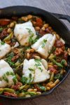 One Pan Chorizo and Cod is an easy and flavorful weeknight meal. Cod, escarole, and white beans get a punch of flavor from spicy, garlicky chorizo. This one pan dish has only 7 ingredients and takes just 30 minutes to prepare, and just as perfect for guests as it is for weeknights.